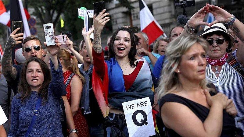 Friedliche Querdenken-Demonstratinnen am 29.8.2020 in Berlin mit Reichskriegsflaggen im Hintergrund und QAnon-Symbol im Vordergrund.